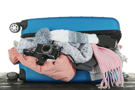 Open suitcase with warm clothes and photo camera on wooden table against white background. Winter vacation concept
