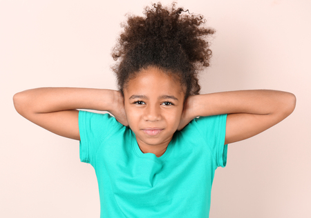 Little African-American girl covering her ears on light background. Hearing problem
