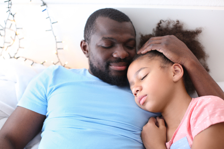 African American man with his daughter in bed. Family bedtime Banque d'images