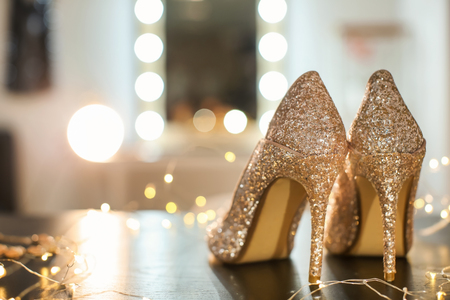 Beautiful high heeled shoes on table with fairy lights Фото со стока