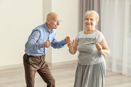 Linda pareja de ancianos bailando en casa