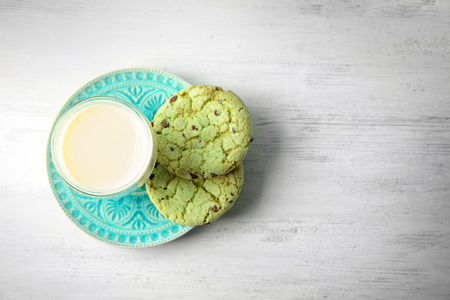 Plate with mint delicious oatmeal cookies and glass of milk on table