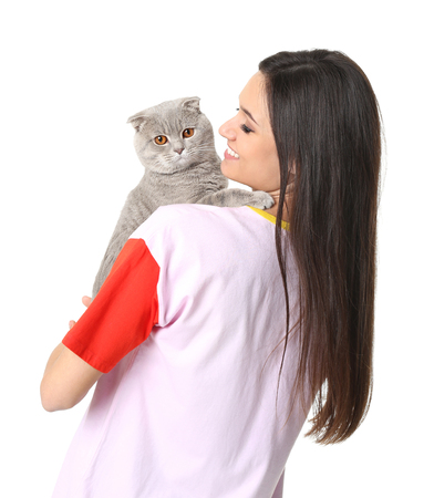 Young woman with cute pet cat on white background Фото со стока