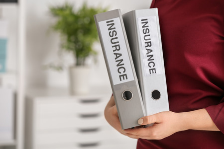 Insurance concept. Woman holding folders, indoors