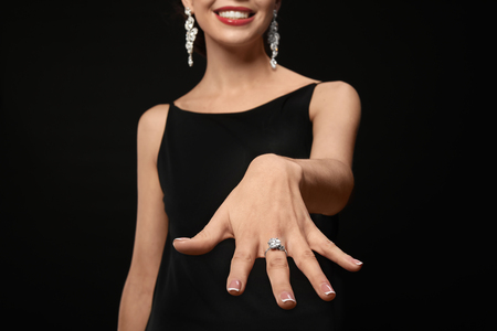 Beautiful young woman with elegant ring on dark background 免版税图像