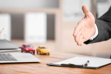 Insurance concept. Man reaching hand for welcoming client over table Stock Photo