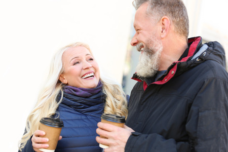 Happy mature couple drinking coffee outdoors on autumn day
