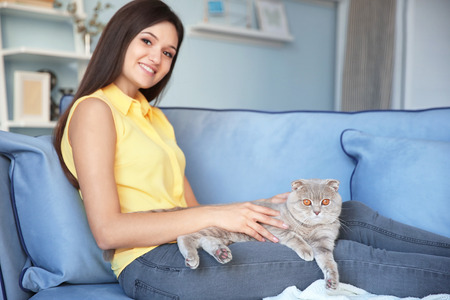 Young woman with cute pet cat at home Фото со стока