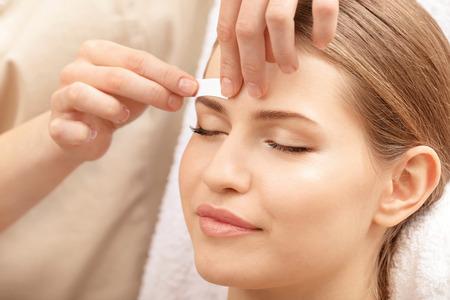 Junge Frau, die Augenbrauenkorrekturverfahren im Salon durchmacht Standard-Bild