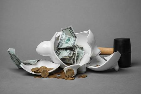 Salvadanaio rotto con soldi e martello su sfondo grigio