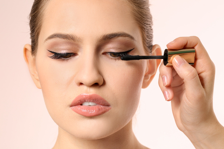 Professional visage artist applying makeup on woman's face on light background Standard-Bild