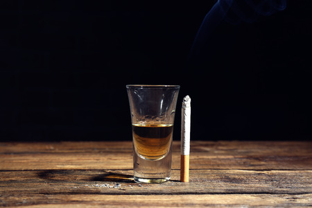 Glass of alcohol and cigarette on table