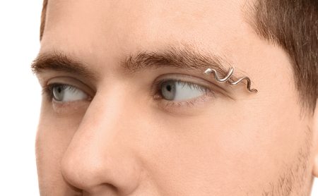 Young man with pierced eyebrow on light background, closeup Stock fotó