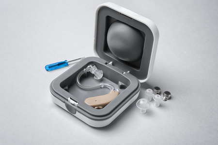 Hearing aid with accessories on light background
