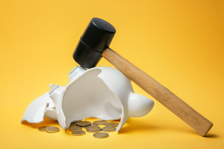 Broken piggy bank with money and hammer on color background 스톡 콘텐츠