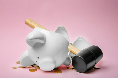 Broken piggy bank with money and hammer on color background Imagens