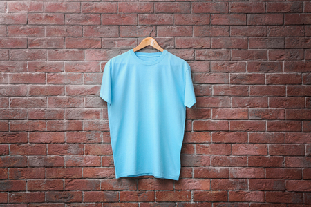 Blue t-shirt on brick wall background. Mock up for design