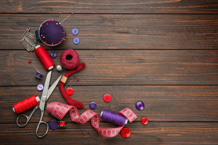 Colorful threads and sewing accessories on wooden background