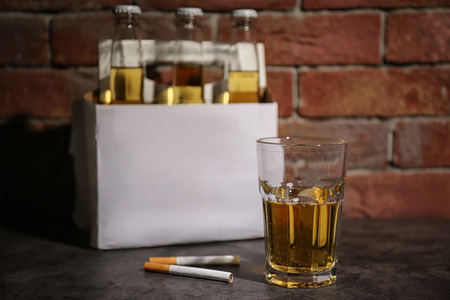Glass of alcohol and cigarettes on table near brick wall