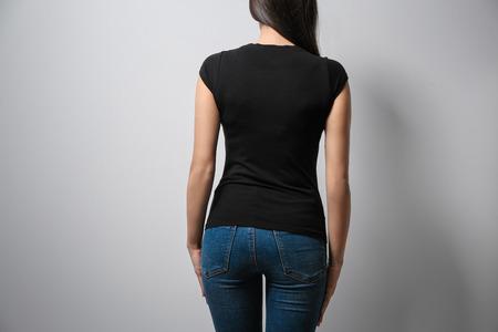 Woman in black t-shirt on light background. Mock up for design 版權商用圖片