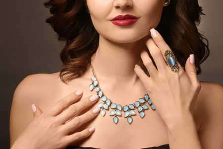 Beautiful woman with elegant jewelry on dark background, closeup