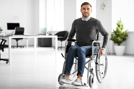 Young man in wheelchair at workplace Imagens