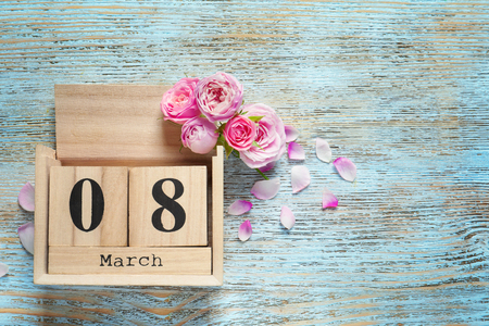 Block calendar and roses on wooden background. International Women's day celebration
