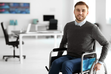 Young man in wheelchair at workplace Stock Photo