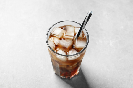 Cold cola in glass on light background