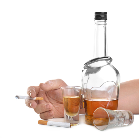 Man in handcuffs holding cigarette near bottle of alcohol on white background Stockfoto