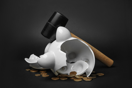 Broken piggy bank with money and hammer on black background 스톡 콘텐츠