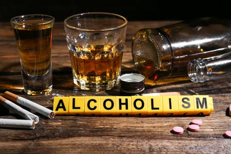 """Composición con la palabra """"alcoholismo"""", cigarrillos y drogas en la mesa"""