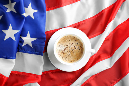 Cup of hot coffee on flag of the USA