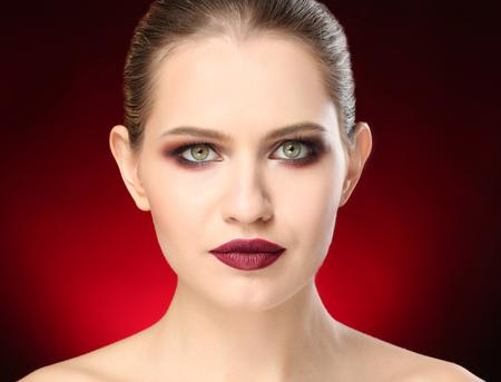 Woman with beautiful makeup on dark background. Professional visage artist work