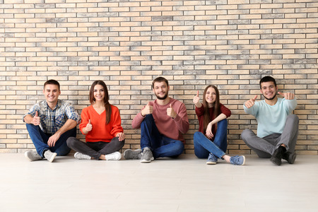 Group of young people sitting on floor together, indoors. Unity concept