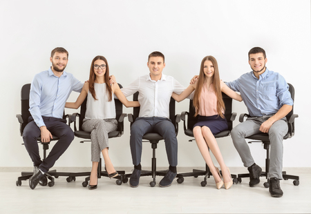 Group of young people sitting together on chairs against white wall. Unity concept Stock Photo