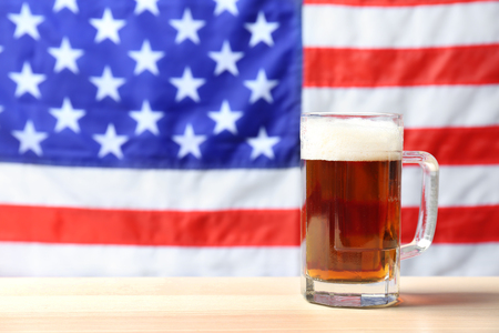 Glass of beer on table against blurred American flag