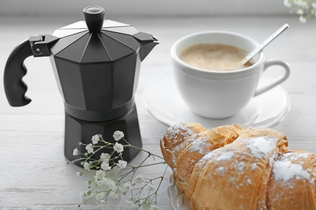 Fresh croissant, moka pot with cup of coffee and flowers on table. Tasty breakfast