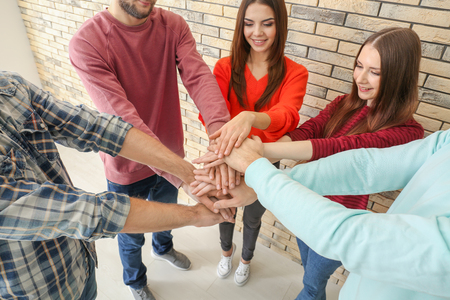 People putting hands together, indoors. Unity concept