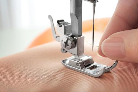Woman using sewing machine, closeup