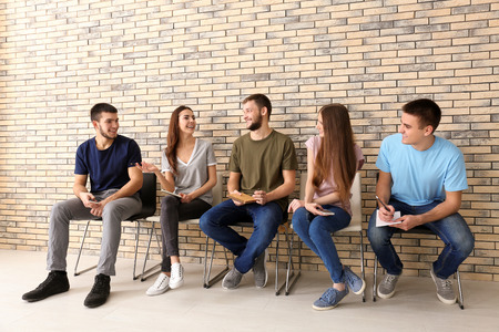 Group of young people sitting on chairs together, indoors. Unity concept