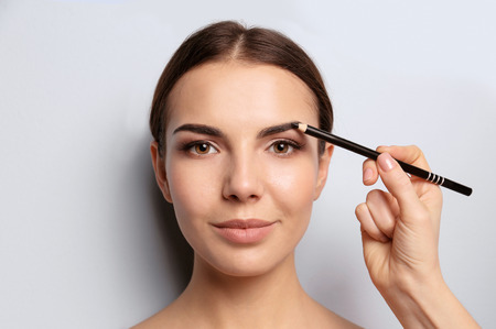 Jeune femme subissant une procédure de correction des sourcils sur fond clair