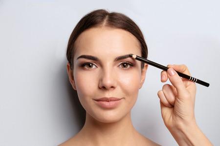 Junge Frau, die sich einem Augenbrauenkorrekturverfahren auf hellem Hintergrund unterzieht