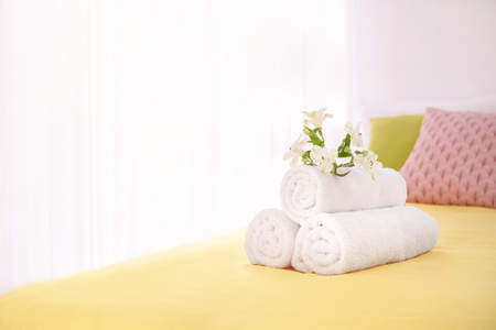 Rolled white towels with flowers on bed 免版税图像