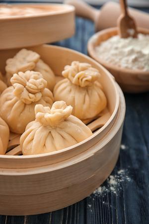 Tasty baozi dumplings in bamboo steamer on table