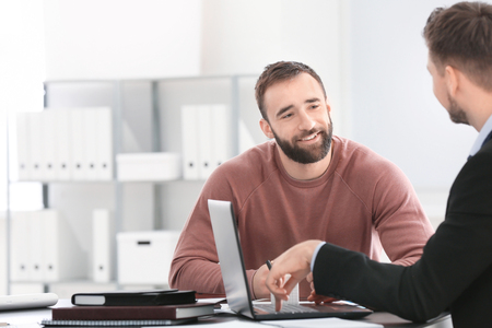 Businessman consulting young man in office Stock Photo