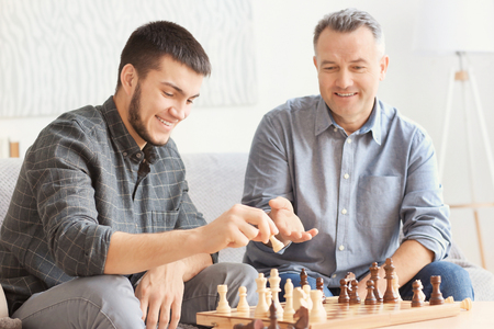 Mature man playing chess with his son at home