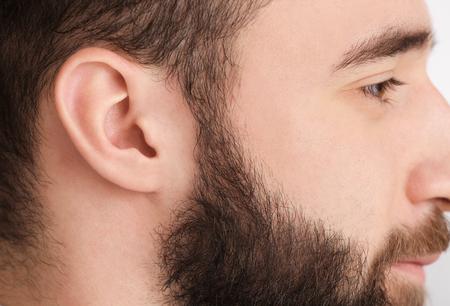 Young man, closeup. Hearing problem