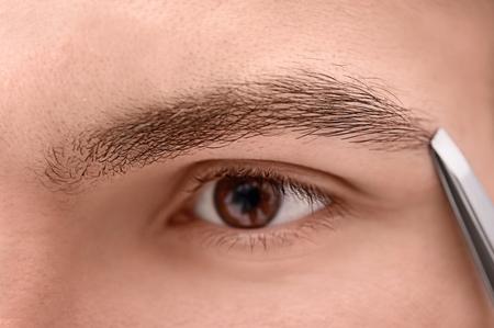 Young man tweezing his eyebrow, closeup