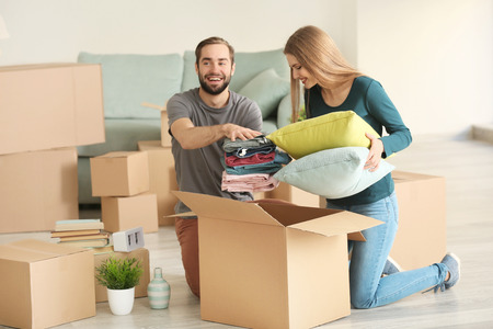 Young couple packing moving boxes in room Stock Photo